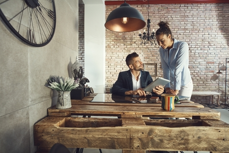 Young businesspeople using tablet at stylish interior. Stock Photo