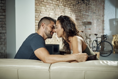 be kissed: Beautiful young loving couple kissing at home on sofa. Stock Photo