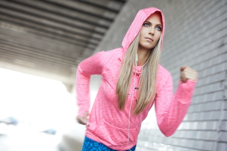Urban life, workout in the big city. Woman wearing colorful sport dress running in a concrete gray tunnel. photo