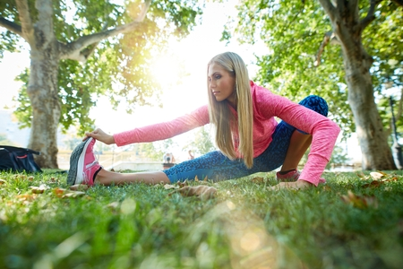 Young woman doing morning workout exercises in citypark after running, sunlight. photo