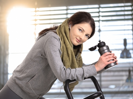 Sporty young woman exercising on machine looking at camera, smiling.
