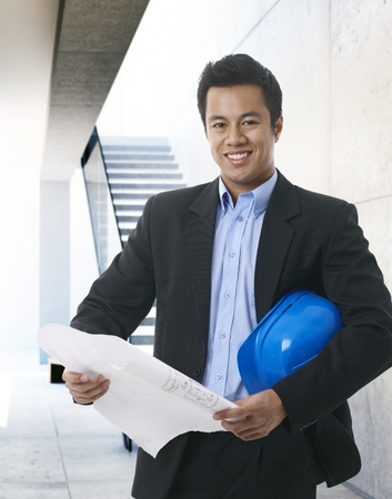 open floor plan: Happy Asian architect holding floor plan and hardhat, smiling, looking at camera.