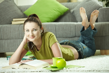 Teenage student girl lying on floor at home doing homework. Looking at camera, smiling.