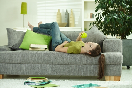 Jonge vrouw liggend op de bank thuis, appel, luisteren naar muziek, boeken verspreid rond. Stockfoto - 79017136