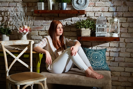 Young ginger woman sitting at vintage home.