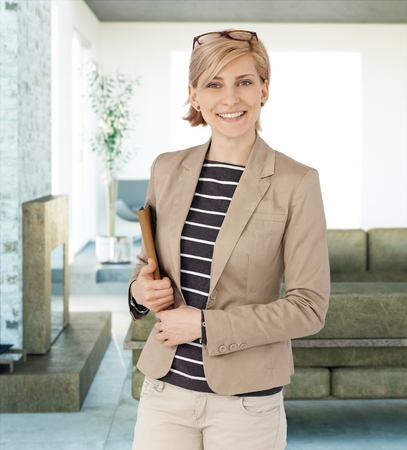Portrait of happy blonde businesswoman smiling, looking at camera, holding folder. photo