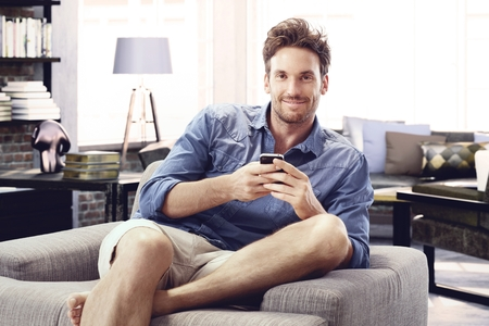 Happy man sitting in armchair at modern loft home using mobile phone. photo