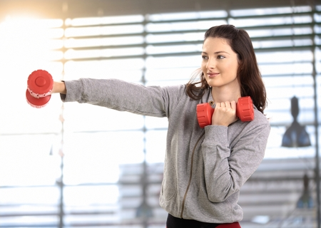 mujeres morenas: Healthy teenage girl boxing with hand barbell, smiling. Foto de archivo