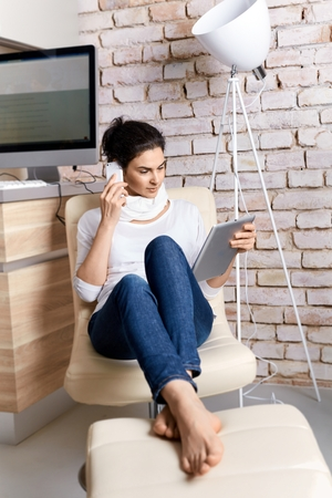 Attractive adult woman working at home on the phone and using tablet.
