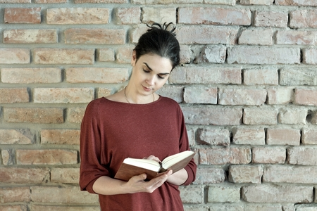 young adult woman: Casual young adult woman standing at wall holding and reading book. Lifestyle portrait photo with copyspace.