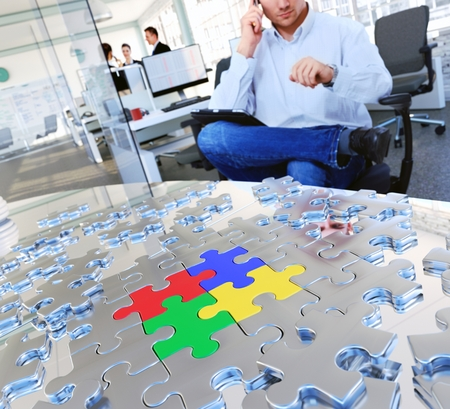 Conceptual business image. Puzzle pieces on meeting table at busy modern office. photo