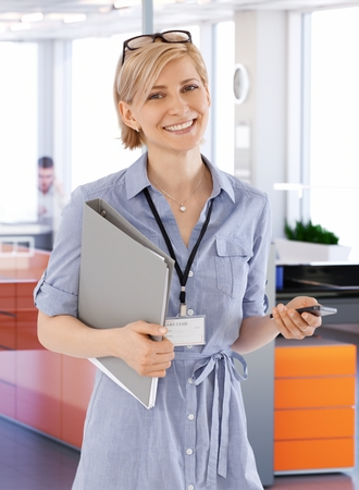Young businesswoman holding folder and mobile, smiling happy. photo