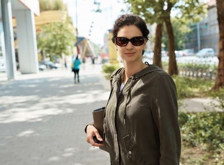aviators: Woman wearing a jacket and sunglasses, outdoor portrait on street. Stock Photo