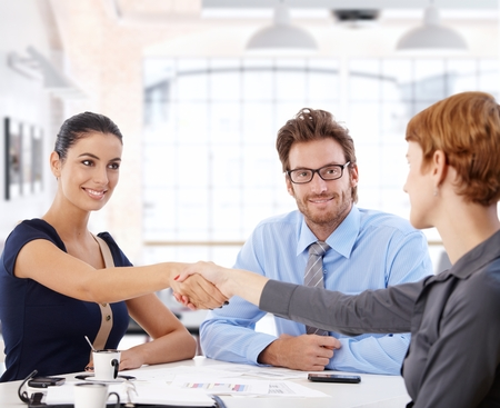 Young businesswomen shaking hands over meeting table, smiling.