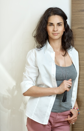 Fashionable attractive young adult woman leaning against wall at home. Wearing Casual clothes, looking at camera, smiling. photo