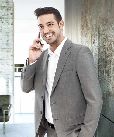 Happy young businessman standing by wall, talking on mobilephone, looking away. photo