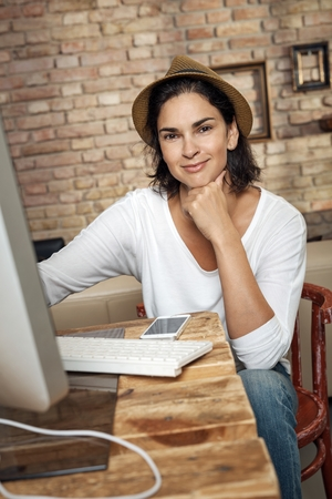Portrait of smiling fashion blogger woman at home holding laptop writing blog post. Stock Photo
