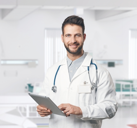 Portrait of confident young doctor using tablet computer in hospital room.