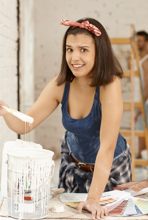 DIY woman looking at paint with disgust at home renovation. photo