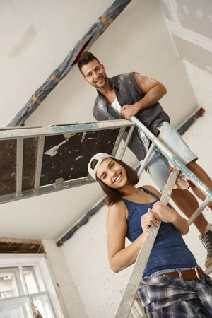 Young couple standing on scaffold, renovating home, smiling happy. photo