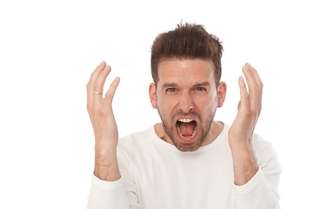 Closeup portrait of angry young man shouting, looking at camera.