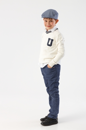 Cool little schoolboy standing with hands in pockets, wearing hat. Stock Photo
