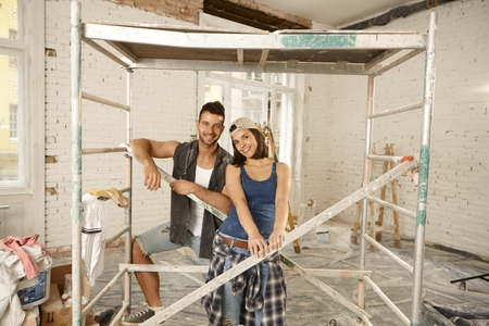 Happy young couple renewing home, smiling under scaffold. photo