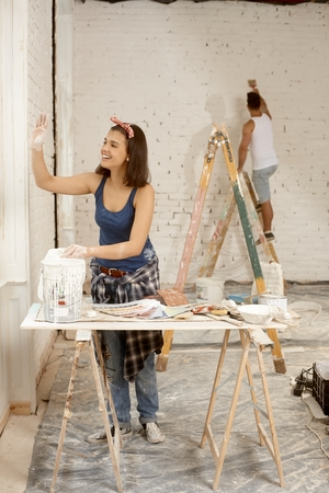Young couple renovating home, woman waving through window to neighbours. photo