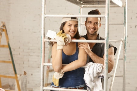 Happy young loving couple renovating home, embracing under scaffold, looking at camera. photo