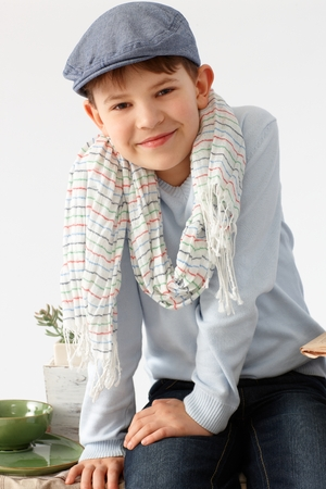 Portrait of charming little boy in hat, smiling, looking at camera. photo