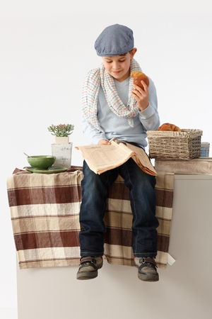 Cute little boy sitting on kitchen counter, reading news, acting as grown up. photo