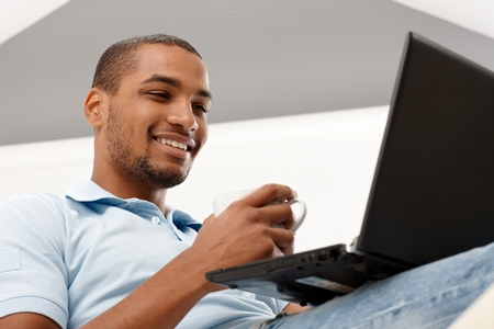 Young black man using laptop computer, smiling happy. High angle view. photo