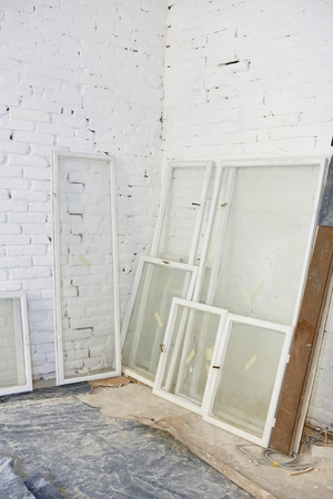 Renovation site with blank wall and windows supported by wall.