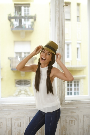 Happy young woman in hat standing front of window, having fun. photo