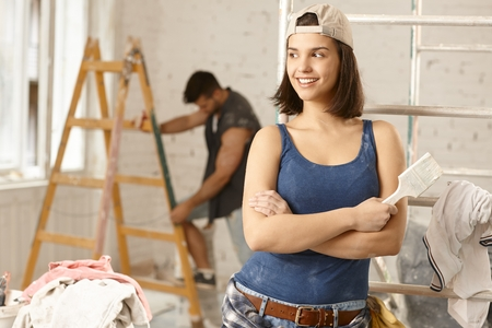 Happy young woman renovating home, standing arms crossed, looking away. photo