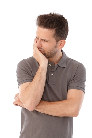 headaches: Young man with painful facial expression, holding chin, turning away head. Stock Photo
