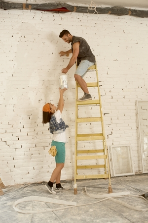 Young couple renovating home, man painting wall on top of ladder, woman lifting painting can up. photo