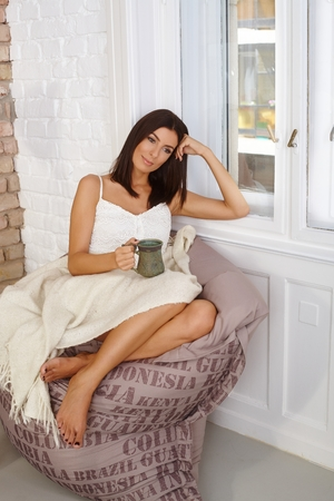 Young woman resting on bean bag chair at home, daydreaming, holding tea mug. photo