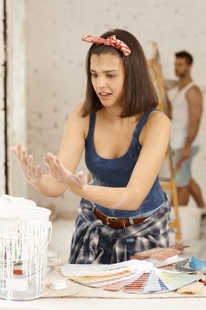DIY woman looking at own hands with horror at home renovation. photo