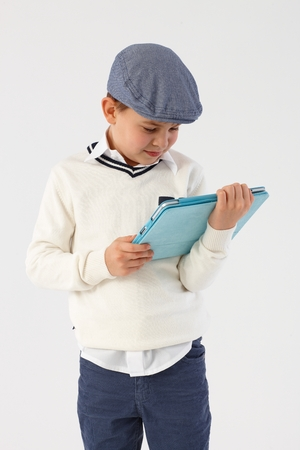Little boy in cool hat using tablet pc. photo