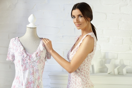 Young fashion designer working, standing by dress-stand. photo