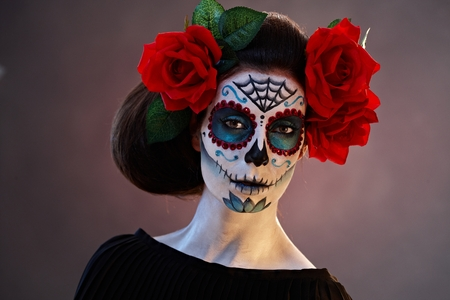 Portrait of scary woman at halloween in mexican santa muerte mask. Stock Photo