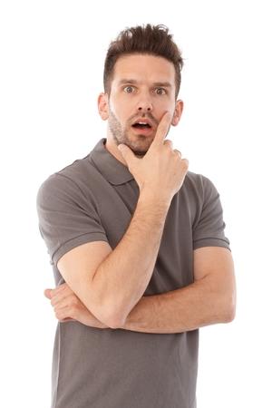 Ritratto di giovane uomo in piedi in piedi con la bocca aperta a mano sul mento.