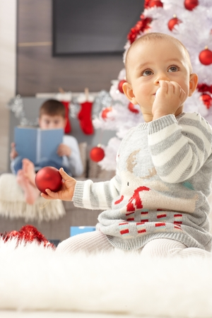 Little girl sitting by christmas tree, playing with ornaments. Stock Photo