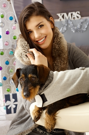Happy young woman smiling, having dachshund in dog suit.