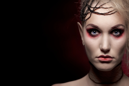 Young blonde woman wearing halloween makeup, looking at camera over black background. Stock Photo