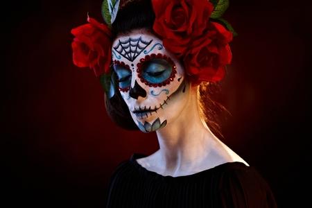 Female portrait in mexican santa muerte mask eyes closed.