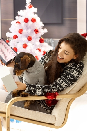 Young woman celebrating christmas with dog, opening present, smiling happy.