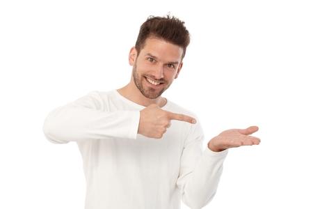 Un jeune homme heureux prétendant tenir quelque chose dans la main gauche, en le montrant d'une autre main. Banque d'images - 85187647