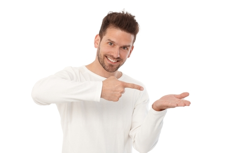 Happy young man pretending to hold something in left hand, pointing to it by other hand.